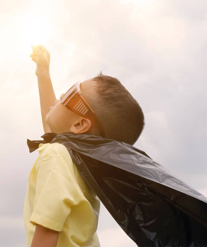 Child wearing googles, fist up to the sky and wearing a cape