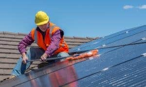 worker on roof fitting solar panels in leicester